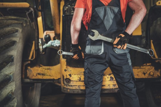 Heavy Equipment Maintenance. Professional Caucasian Industrial Mechanic with Tools in Hands in Front of Small Construction Bulldozer.